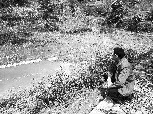 3月30日,云南普洱云仙乡水务站站长欧学成看着几乎干涸的哑巴山水库,水库的管道已经堵塞。本报记者 陈宁一 摄