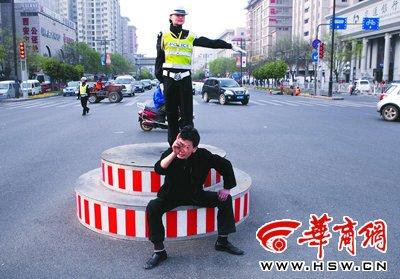 昨日下午5时54分,在西安西华门十字,一男子坐在岗台上醉言醉语,岗台上的女警面带微笑照常执勤 本报记者 赵雄韬 摄