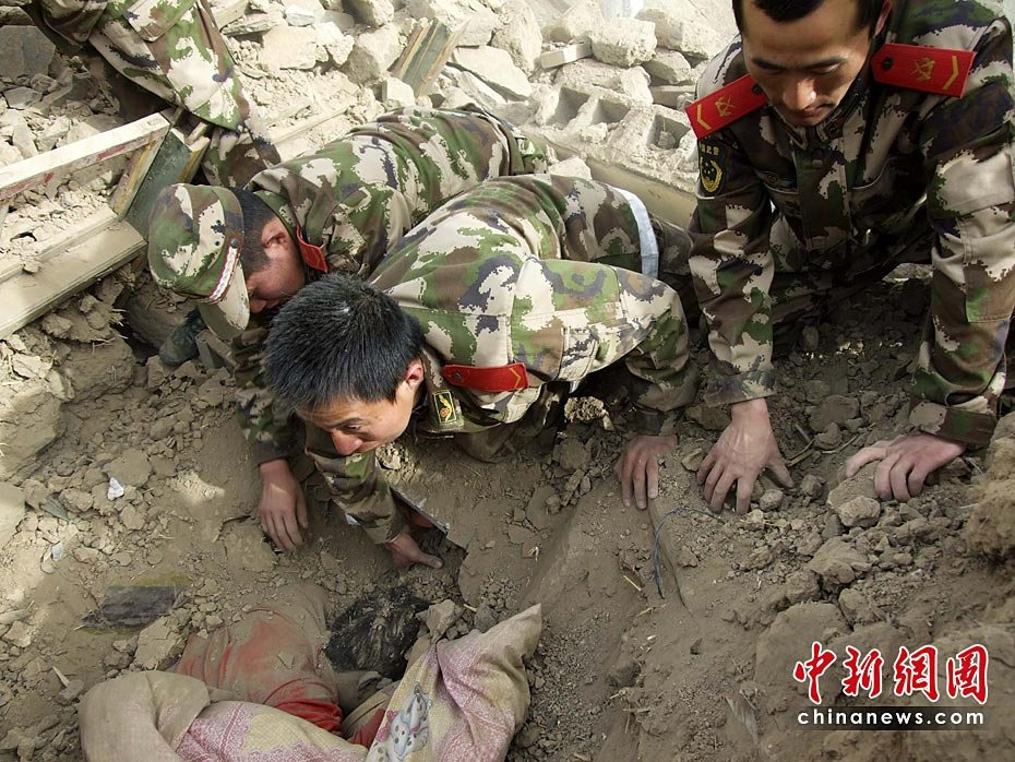 图为4月14日11时,武警玉树支队的战士在玉树县结古镇地震废墟里救助被困民众。