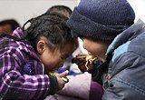两名受灾孩童分食一盒方便面