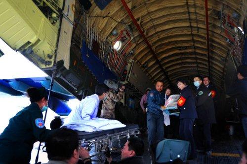 第一批伤员被抬下飞机。