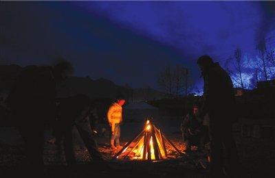 一名小男孩在篝火边取暖。