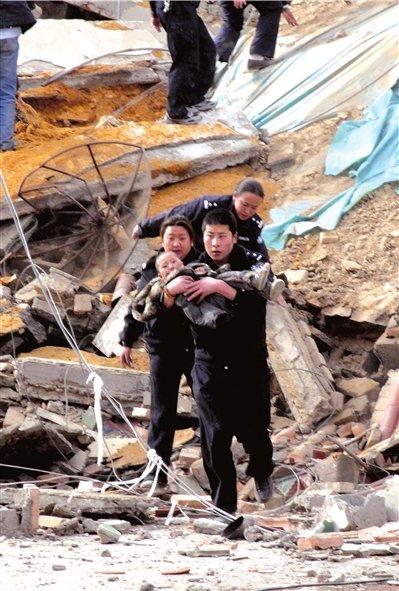 救援人员抱着孩子急匆匆奔向治疗点。