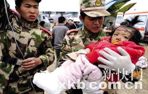 两名武警官兵把刚刚救出的一岁半的藏族小姑娘桑周多杰送往玉树机场,广空运输航空兵某团团长王全胜机组将其送到了格尔木抢救,小姑娘的母亲已经遇难,父亲生死未卜。新快报特派通讯员 沈玲/摄