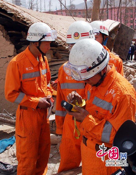 王建与队友们正在地震现场紧张进行救援行动。周才钧摄影