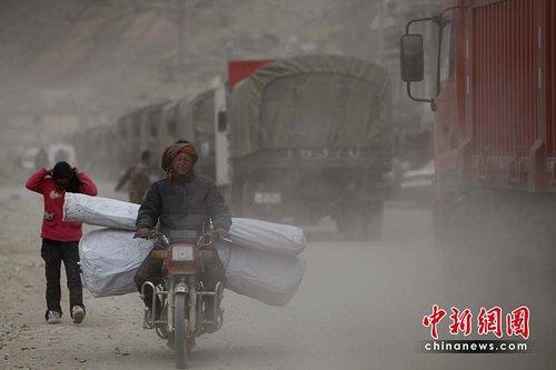 图文:领取救灾物品的受灾民众行走在尘土中