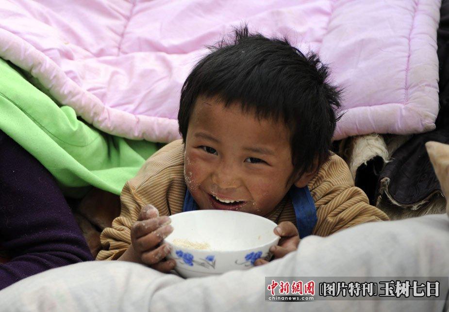 图为青海玉树体育场地震民众安置点,一名孩童欢快地吃东西。中新社发  廖攀 摄
