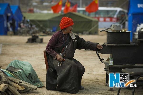 4月20日,在青海玉树结古镇,一位藏族老阿妈在安置点的帐篷外为炉灶添柴禾。新华社记者周磊摄