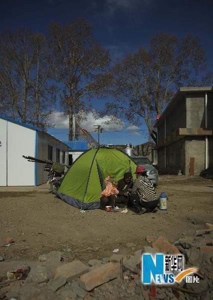 4月20日,在青海玉树结古镇,一名小女孩在用作临时住所的帐篷外吃方便面。新华社记者周磊摄