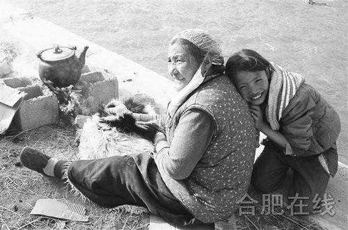 一对藏族祖孙用最古老的羊皮鼓风箱吹火烧水