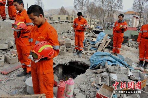 地震救援队在玉树地震灾区废墟上默哀