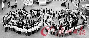 """亚运志愿者聚集在广州城市职业学院广场,手牵手围成两个相交的""""心形""""。 记者黎旭阳摄"""