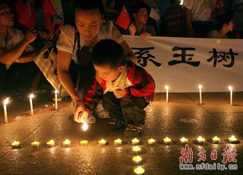 昨天晚上,数千名佛山市民自发聚集在南海千灯湖为玉树地震死难同胞默哀。图为一位妈妈带着孩子点燃蜡烛。南方日报记者 张由琼摄