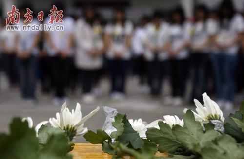 广州城市职业学院的学生手持菊花在广场上向遇难同胞默哀。