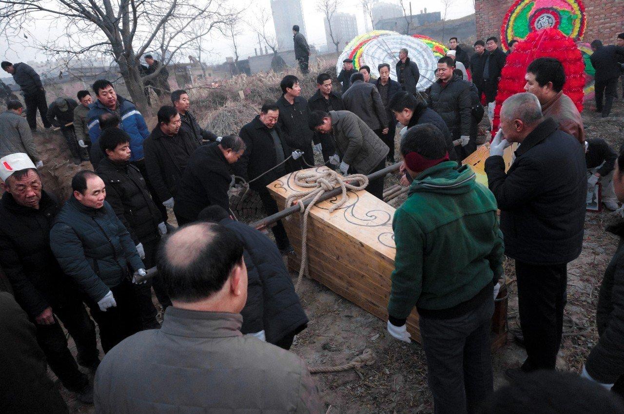 下葬仪式开始。队里的乡亲们抬着棺材到了墓地准备下葬。