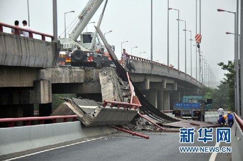 15日凌晨,杭州钱江三桥辅桥主桥面右侧车道部分桥面突然塌落,一辆重型半挂车从桥面坠落,又将下闸道砸塌。司机跳车受伤,送往医院救治。 新华社记者 王定昶 摄