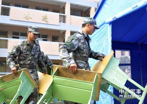 5名受伤战士伤愈后正在搬运课桌,为该校复课做好准备