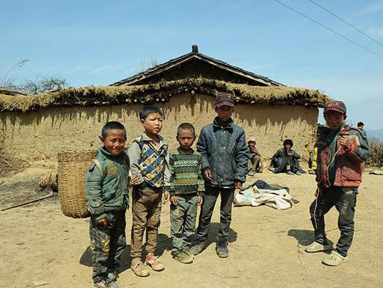 四川省大凉山区美姑县拉木阿觉乡马依村的几名孩子站在村里的一处空地上(3月25日摄)。 新华社记者 陈地 摄