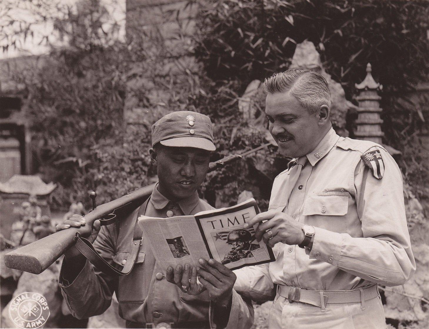 中国战区协调员、来自爱荷华州达文波特的韦恩・蒂森中校,正在向一位中国警卫展示一本《时代周刊》。汤马斯・梅尔文五级技术军士拍摄于中国昆明,1945年6月29日。