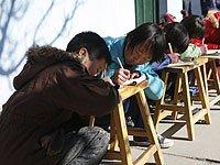 甘肃榆中孩子室外写作业晒太阳取暖