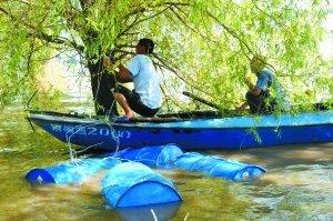 昨日,在吉林省榆树市五棵树镇,两村民将打捞上来的原料桶绑在树上以免被冲走。新华社发