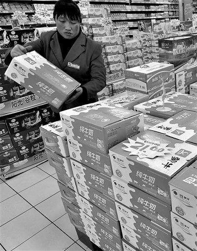 """昨日,山东邹平县一超市内,工作人员在整理蒙牛牛奶。受""""蒙牛检出强致癌物""""影响,山东一些超市蒙牛纯牛奶少有人问津。董乃德 摄"""