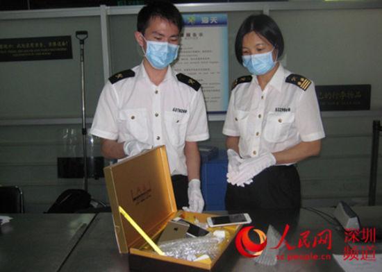 深圳皇岗海关工作人员展示大红袍茶叶盒藏iPhone 6。(深圳皇岗海关供图)