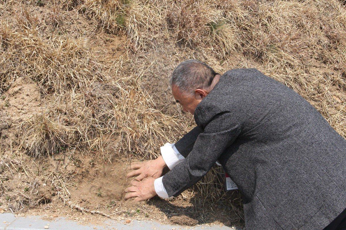 陈亚洲边哭边用手在8号墓上刨土。他和女儿从家里带来了一个锦袋,准备装一些土带回家,放在母亲的骨灰盒旁边。