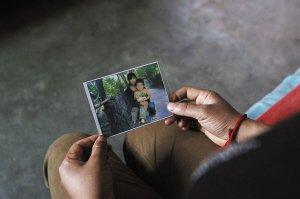 杨其聪的儿媳拿着自己和儿子的照片 文若愚 摄