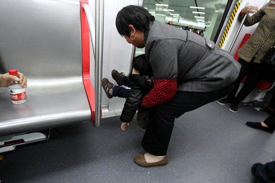 """2012年11月20日,杭州地铁免费体验的第三天,根据杭港地铁公司的统计,当地约有7万人体验地铁1号线,和前两天总人数相当。其中,大伯大妈的热情,被彻底点燃,多趟列车近乎满载,难以上客。同时,车厢内竟然还出现了家长抱着孩子往车门边、座位下小便的状况,有网友戏称:杭州地铁的""""第一次""""没开通就被剥夺了。图片CFP"""
