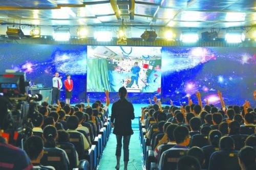 20日上午,在中国人民大学附属中学太空授课地面课堂,学生们举手向航天员王亚平提问。