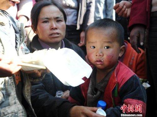 11月11日,距离云南师宗煤矿事故过去近31个小时,20名遇难者遗体已升井,仍有22人下落不明。图为遇难者赏德强两岁的小儿子在警戒线外守候。中新社发 史广林 摄