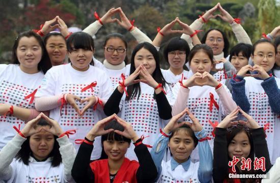"""11月30日,来自南京农业大学红十字会学生分会的百余名大学生志愿者来到玄武湖等地,举办以""""行动起来,向'零'艾滋迈进""""为主题的公益活动,通过与贴有""""我是艾滋病患者,抱抱我好吗""""字样的大熊相互拥抱、舞动神曲""""小苹果""""、发放防艾红丝带等互动活动,向民众宣传艾滋病防治知识,呼吁关爱艾滋病人。12月1日是第27个""""世界艾滋病日"""",今年世界艾滋病日活动主题仍为""""行动起来,向'零'艾滋迈进"""",副标题为""""凝聚力量,攻坚克难,控制艾滋""""。泱波 摄"""