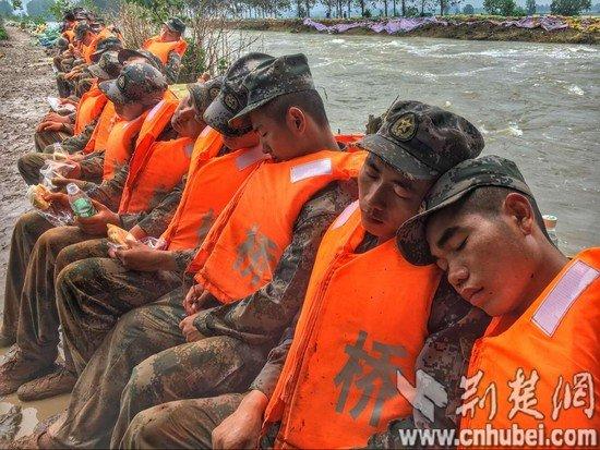 连续奋战 25 小时 舟桥旅官兵拿着面包睡着了