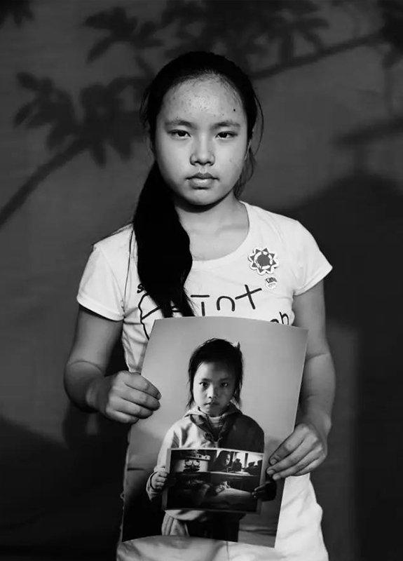 """2014年5月4日,四川省江油市。""""汶川地震""""6周年,地震幸存者13岁的梁可馨拿着地震1周年时拍摄的肖像。现在,她是江油市实验中学读初一学生。"""