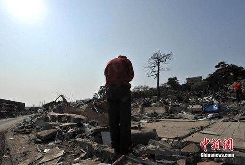 """4月21日,日本宫城县石卷市遭遇""""3.11""""地震海啸又引发燃气失火烧毁的极重灾区大片废墟上,一位红衣女子为遇难亲人默默致哀。中新社记者 贾国荣 摄"""