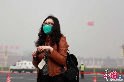 3月8日,第十二届全国人民代表大会第一次会议在人民大会堂举行第二次全体会议,女记者为避雾霾天戴口罩报道两会。中国网董德摄影