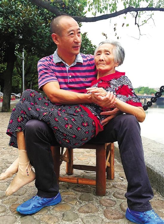 好暖!儿子怀抱82岁老母江边聊天 被赞大孝子