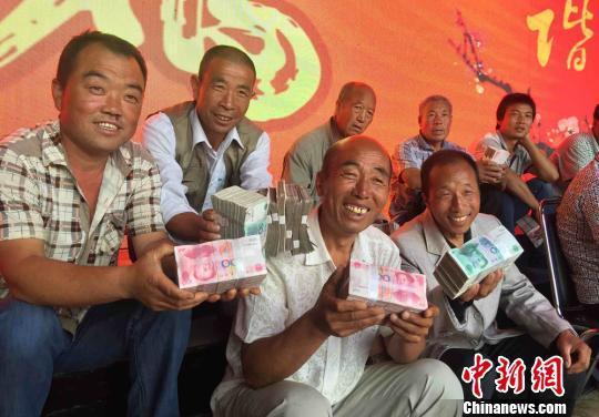 """百元大钞堆""""钱山"""":村支书千万现金分红村民"""