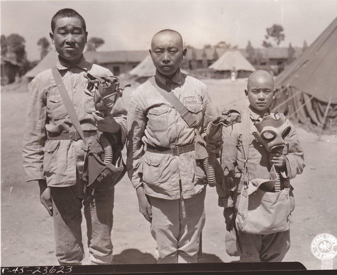 三个脸型大小不同的中国士兵正在测试不同类型的防毒面具。从左到右为:美式轻便型面具,美军现役防毒面具,英国制造防毒面具。西摩・萨摩雷尔一等兵拍摄于中国昆明,1945年4月17日。