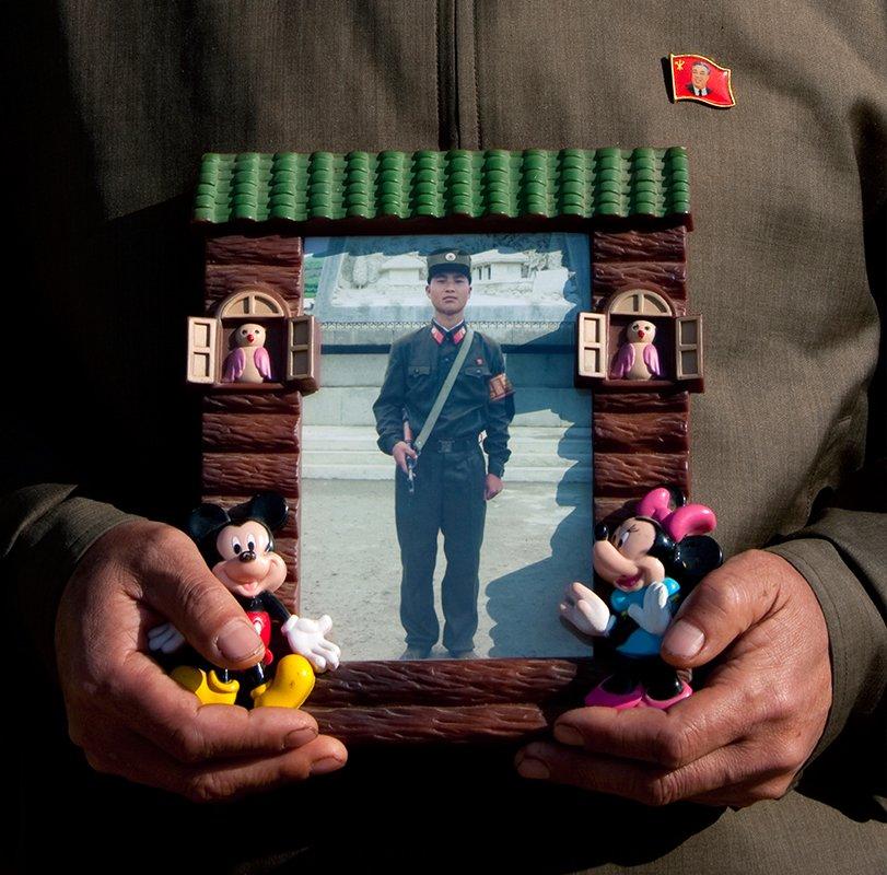 """一个米老鼠相框里面放着一张年轻士兵的照片。看到我好奇的目光,村长说到:""""这是我儿子,他正在服兵役。""""当我问到什么时候他儿子才可以退役回家时,他答道:""""一直到祖国统一。"""""""