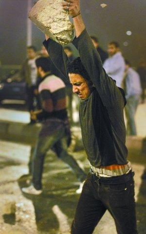 25日,示威者砸碎混凝土路障。