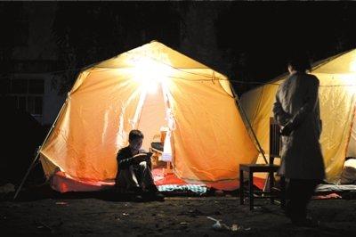 昨晚,在雅安市芦山县人民医院安置点,一名男子在帐篷外翻看手机。京华时报记者潘之望摄