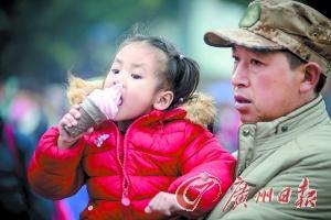广州近日依然保持低温天气,广州火车站站前广场,一位不怕冷的小姑娘在寒风中吃冰淇淋。广州日报记者陈忧子 摄