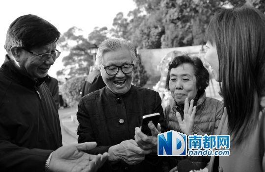 邓先群(左二)看到小平当年在中山时的资料图后一脸兴奋,旁边的女子是当年与邓小平合过影的谭志颖。 南都记者叶志文摄