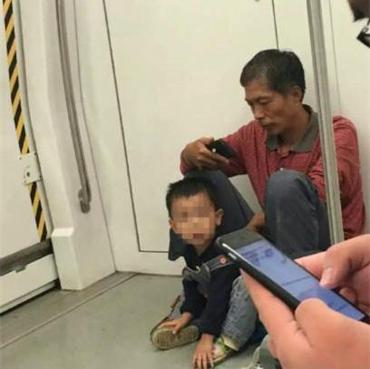 民工乘地铁不坐空位 怕弄脏座椅带孩子坐地上