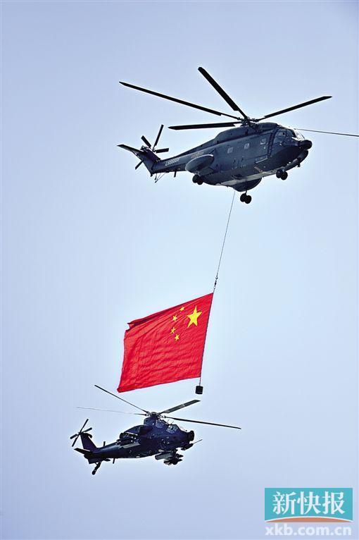 悬挂着中华人民共和国国旗和中国人民解放军军旗的空中护旗方队率先飞过天安门,方队由26架直升机和7架教练机组成。新华社发
