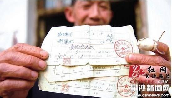 龙孟雄向记者展示1958年时的存款单,上面的姓名、时间、金额还十分清晰,三张存款合计26元。康子弘摄