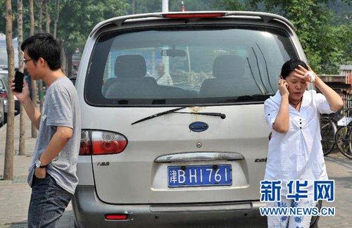 5月28日,在天津市区,感到明显震感的市民跑出户外给亲友打电话。 新华社记者 岳月伟 摄