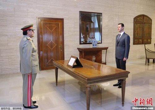 当地时间2012年7月19日,叙利亚大马士革,叙利亚新任国防部长法赫德·贾西姆·弗拉杰(左)在总统巴沙尔面前宣誓就职,接替18日在自杀式爆炸袭击中遇难的前国防部长乌德·拉杰哈。